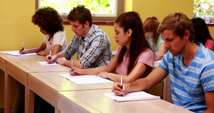 Focused students sitting in a line writing in classroom Stock Photos