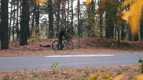 Focused stylish young professional cyclist in black cycling apparel, helmet and sports glasses starts riding on road bike in fall. Park. Handsome male athlete stock video