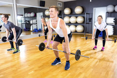 Focused team doing deadlift exercises with weights at fitness gym Royalty Free Stock Photography