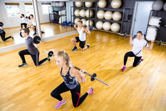 Focused team doing split squats with weights at fitness gym Stock Photos