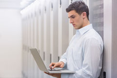 Focused technician typing on his notebook. And leaning against a tower in a large data center royalty free stock images
