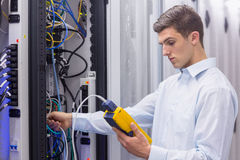Focused technician using digital cable analyser on servers Stock Images