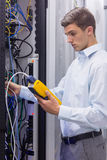 Focused technician using digital cable analyser on servers Royalty Free Stock Photography