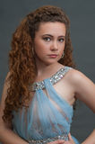 Focused teen beauty head shot in light blue dress to left. Royalty Free Stock Images