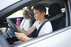 Focused teenager driving a car with his mother Royalty Free Stock Images