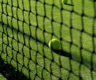 Focused tennis ball behind the nett. In a sunny day in May Royalty Free Stock Photography