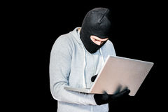 Focused thief with hood typing on laptop Royalty Free Stock Image
