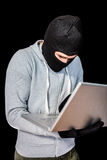 Focused thief with hood typing on laptop Stock Photography