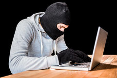 Focused thief with hood typing on laptop Stock Images