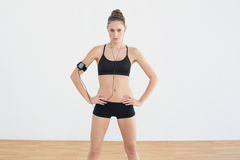 Focused toned woman posing with hands on hips looking at camera Royalty Free Stock Photo