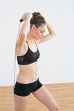 Focused toned woman skipping with rope Royalty Free Stock Photography