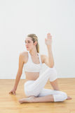 Focused toned woman stretching her body sitting on floor Royalty Free Stock Images