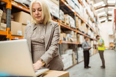 Focused warehouse manager working on laptop Stock Image