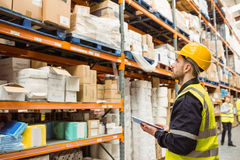 Focused warehouse manager writing on clipboard Royalty Free Stock Images