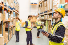 Focused warehouse manager writing on clipboard Stock Photography