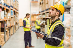 Focused warehouse manager writing on clipboard Stock Image