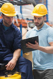 Focused warehouse workers talking together Royalty Free Stock Image