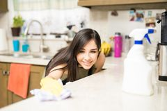 Focused woman cleaning stains in kitchen counter. Close-up of smiling young housewife cleaning dirty kitchen counter with rag royalty free stock photos