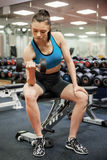 Focused woman lifting dumbbell while sitting down Royalty Free Stock Photography