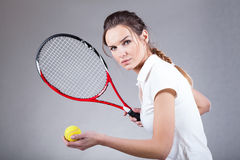 Focused woman playing tennis. On  background Royalty Free Stock Photo