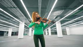 Focused woman is playing the violin in the hall. 4K stock video