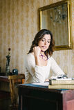 Focused woman reading at vintage workplace Stock Images