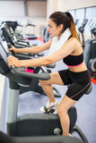 Focused woman using the exercise bike Royalty Free Stock Photo