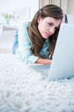 Focused woman using her laptop lying on the floor Royalty Free Stock Photo
