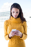 Focused woman using her smartphone. Outside Stock Image