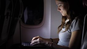 Focused woman work on computer in airliner at night. Busy girl work on computer at airliner stock footage