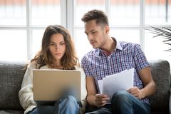 Focused worried couple paying bills online on laptop with document. S sitting together on sofa at home, serious confused men and women planning budget expenses royalty free stock images