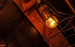 Focused yellow light glass bulb with fixture and gradient light. And shadows pattern with the hanging wire on it royalty free stock photos