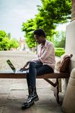 Focused young Afro american female college student looking deep in thought while sitting on a bench working on a laptop on campus stock photography