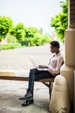 Focused young Afro american female college student looking deep in thought while sitting on a bench working on a laptop on campus stock photos