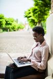 Focused young Afro american female college student looking deep in thought while sitting on a bench working on a laptop on campus stock images