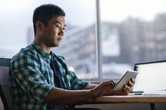Young Asian designer using a tablet at his office workstation. Focused young Asian designer using a digital tablet while sitting alone at his desk working late Stock Images