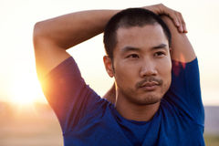 Focused young Asian man stretching his shoulders before a run. Focused and fit young Asian man stretching his arms before going for a solo run outside on a sunny Royalty Free Stock Photography