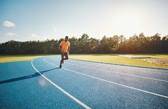 Focused young athlete running alone on a race track. Focused young African male athlete in sportswear sprinting alone along a running track on a sunny day royalty free stock images