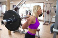 Focused young beautiful girl lifting weights in a gym Stock Images