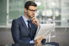 Focused Young Businessman Reading The Newspaper In A Cafe royalty free stock photos