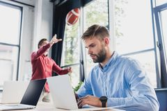 focused young businessman using laptop while colleague playing with rugby ball behind stock images