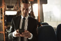 Young businessman standing on a bus sending text messsages stock image