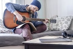Focused composer plays written music on an acoustic guitar while looking at a notebook and with a pencil in his mouth, sitting on. Focused young composer plays royalty free stock photos