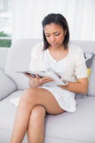 Focused young dark haired woman in white clothes reading magazines Royalty Free Stock Photography