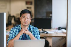 Focused young designer working at his desk in an office. Portrait of a focused young Asian designer sitting at his workstation while working late in a modern Royalty Free Stock Photos