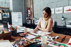 Focused young female artist drawing sketches using colored pencils sitting at her stylish workshop.  Royalty Free Stock Photography