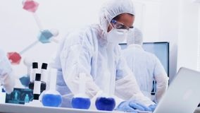 Focused young female scientist in coverall protection equipment typing report on laptop. Female scientist in coverall equipment holding and looking at est tube stock footage