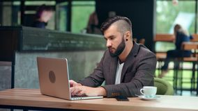 Focused young freelancer man with trendy hairstyle working on laptop pc sitting at public cafe place. Medium shot. Handsome businessman chatting looking at stock video