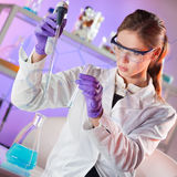 Attractive young scientist pipetting. Royalty Free Stock Image