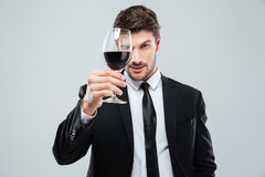 Focused young male sommelier looking at red wine in glass. Focused young male sommelier in suite looking at red wine in glass over white background Royalty Free Stock Photography